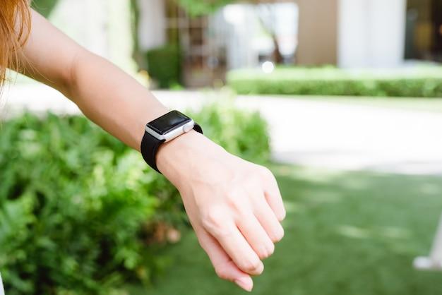 Chiuda su di giovane donna asiatica che considera il suo smartwatch nel giardino verde sulla mattina di fine settimana. yo