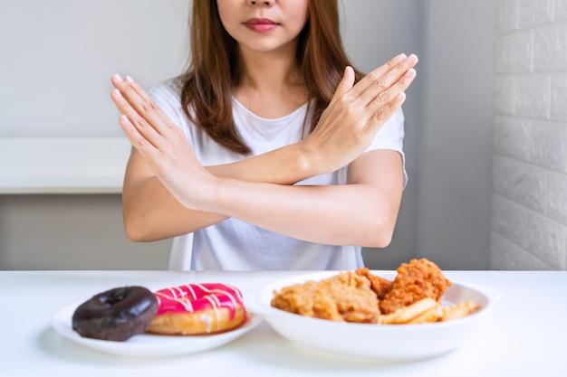 Chiuda su di giovane donna asiatica che fa il segnale delle mani nell'incrocio per negare gli alimenti industriali