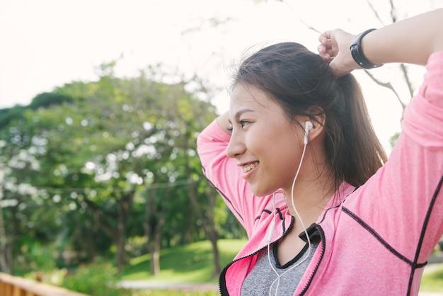 Chiuda su di giovane donna asiatica felice che riscalda il suo corpo allungando il suo corpo