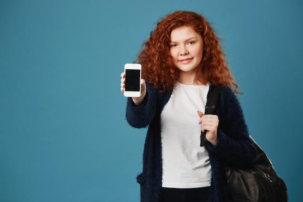 Chiuda su di giovane donna dello studente dello zenzero con capelli ondulati e le lentiggini che indossano la maglietta bianca e il cardigan nero che mostrano lo smartphone.