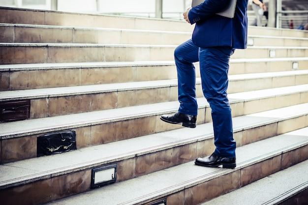 Chiuda su di giovane uomo d'affari che cammina di sopra fuori dell'ufficio.