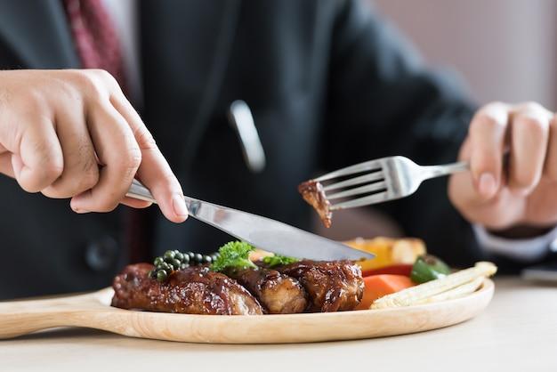 Chiuda su di giovane uomo d'affari che mangia la costata sul vassoio di legno al ristorante.