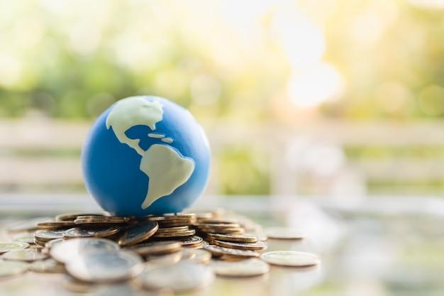 Chiuda su di mini palla del mondo sul mucchio delle monete di oro con il fondo verde della natura e copi lo spazio.