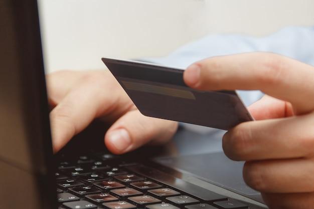 Chiuda su di un uomo che compera online facendo uso del computer portatile con la carta di credito