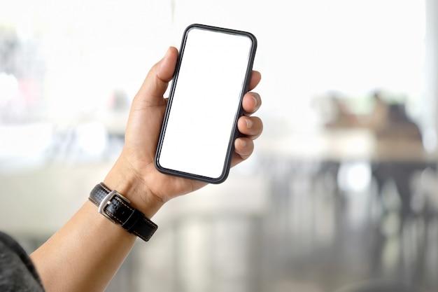 Chiuda su di un uomo che utilizza lo smart phone mobile dello schermo in bianco sopra il fondo vago del bokeh.