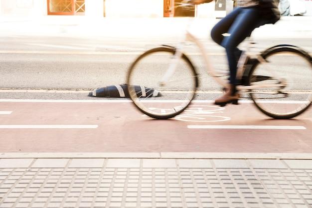 Chiuda su di una bici di guida della donna in pista ciclabile