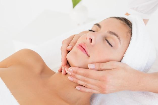 Chiuda su di una giovane donna attraente che riceve il massaggio facciale al centro della stazione termale
