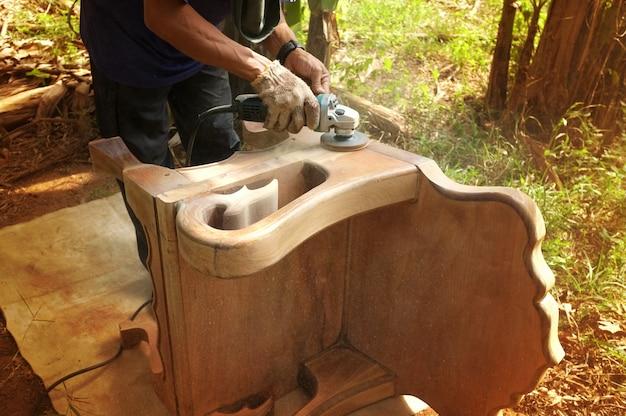 Chiuda su di una sedia di legno di sfregatura del carpentiere con l'impianto di lavaggio elettrico tenuto in mano.