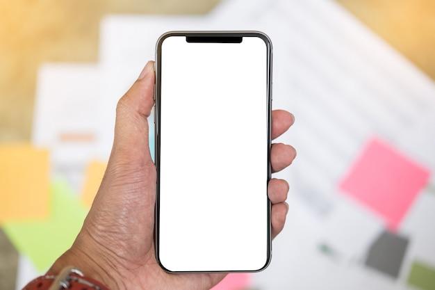 Chiuda su di uno smartphone della tenuta dell'uomo con il cellulare ed il computer portatile dello schermo in bianco alla caffetteria.