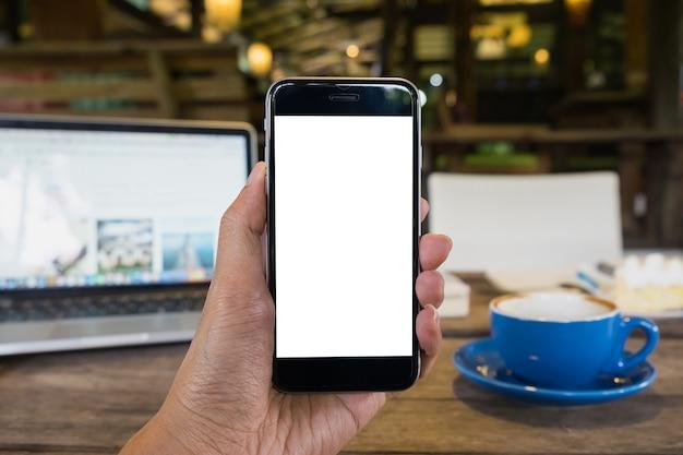 Chiuda su di uno smartphone della tenuta dell'uomo con il cellulare ed il computer portatile dello schermo in bianco