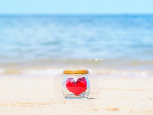 Chiuda su forma rossa del cuore del cuscino in bottiglia di vetro sulla spiaggia dell'estate.