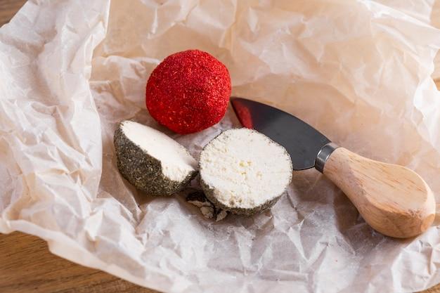 Chiuda su formaggio tagliato a metà sulla tavola