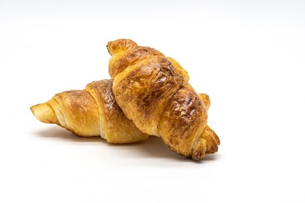 Chiuda su fresco dell'isolato del croissant su fondo bianco.