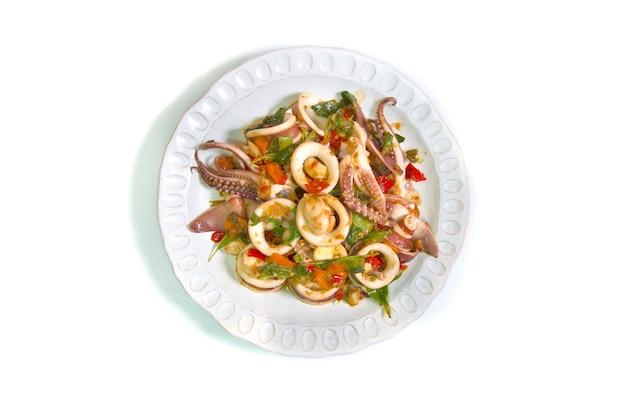 Chiuda su fritto con il calamaro del basilico sul piatto isolato su fondo bianco