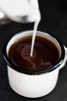Chiuda su latte versato in caffè nero