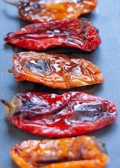 Chiuda su pepe arrostito rosso e giallo con olio d'oliva su un vassoio di pietra.