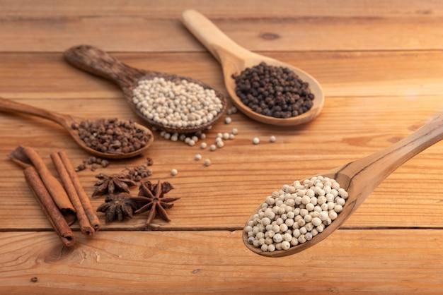 Chiuda su pepe bianco nei bordi di legno del cucchiaio con la polvere della spezia sulla tavola di legno