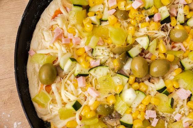 Chiuda su pizza cruda in padella con gli ingredienti
