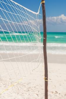 Chiuda su rete da pallacanestro alla spiaggia esotica tropicale vuota