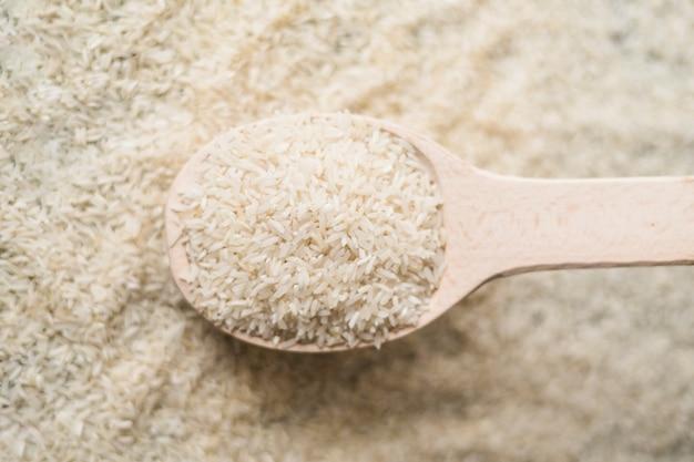 Chiuda su riso crudo in cucchiaio di legno sul fondo del riso