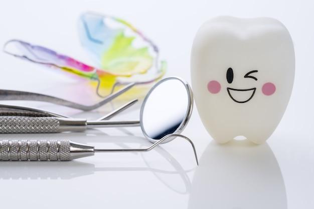 Chiuda su strumenti di dental e denti di sorriso modellano su fondo bianco.