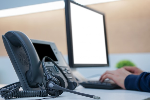 Chiuda su sul telefono della cuffia con l'impiegato che lavora alla tavola da tavolino nel concetto della stanza dell'ufficio