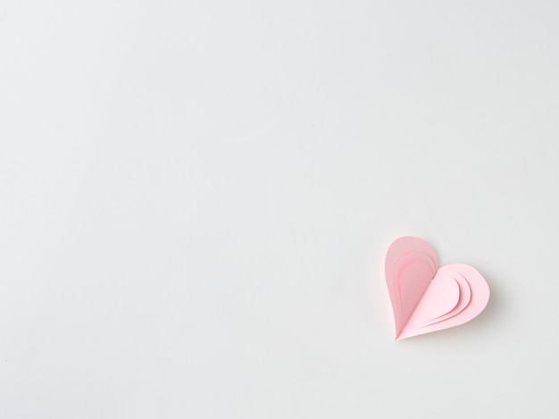 Chiuda su sulle mani femminili che tengono i presente rosa del cuore per il giorno di s. valentino, il compleanno, madre