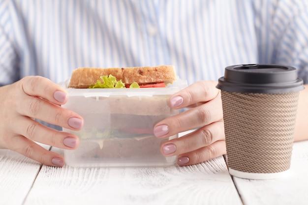 Chiuda su sulle paia delle mani femminili che rimuovono un panino al prosciutto integrale sano sano dal suo contenitore di pranzo durante l'intervallo di pranzo