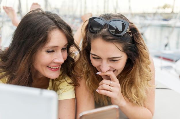 Chiuda su un ritratto di due amiche emozionanti con i telefoni cellulari che si trovano giù e che ridono e che guardano a porte chiuse.