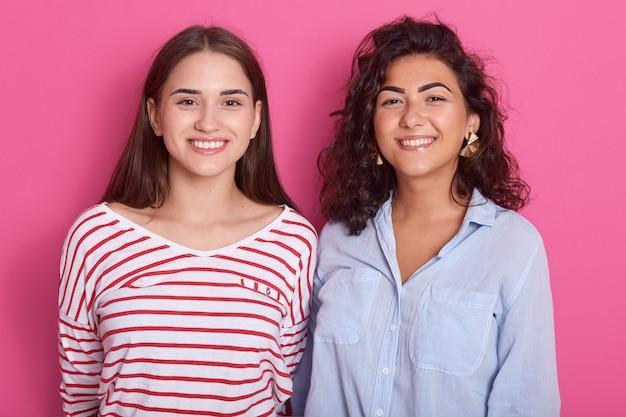 Chiuda su un ritratto di due donne sorridenti caucasiche dai capelli scuri isolate sopra la parete rosa