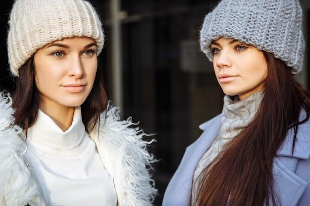 Chiuda su un ritratto di due giovani donne degli amici bei in autunno