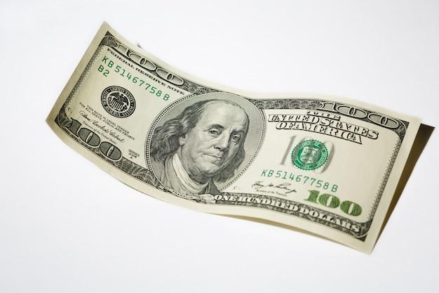 Chiuda su una banconota da cento dollari su bianco