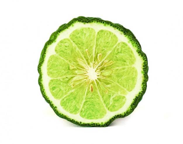 Chiuda su una metà del taglio della frutta e della foglia del bergamotto su fondo bianco