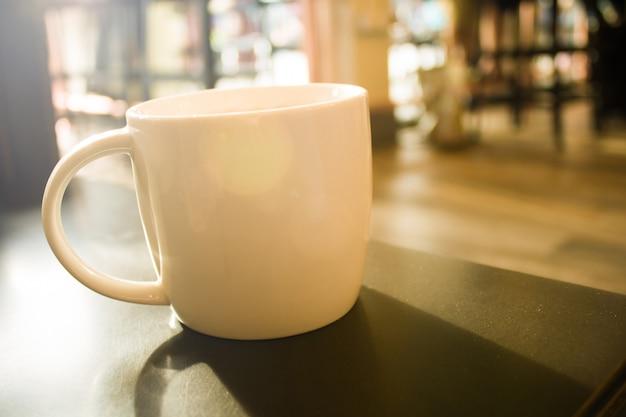 Chiuda su una tazza di caffè bianca sull'effetto nero del filtro dal chiarore del sole della tavola