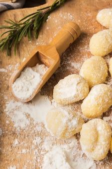 Chiuda sugli gnocchi di patate crudi con farina
