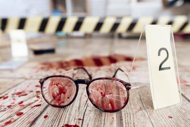 Chiuda sugli occhiali macchiati sangue alla scena del crimine.
