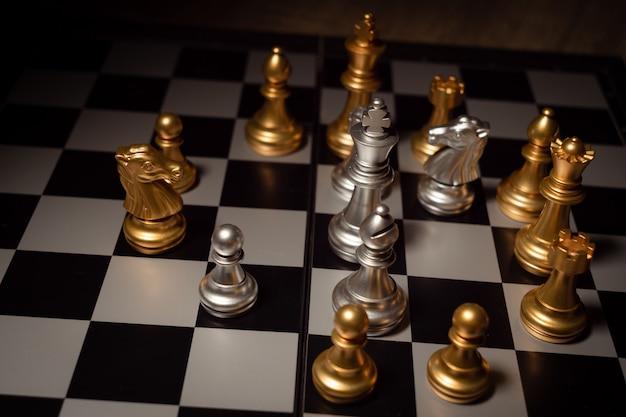 Chiuda sugli scacchi del colpo sul gioco da tavolo con il concetto scuro della concorrenza di processo di tono e dell'umore