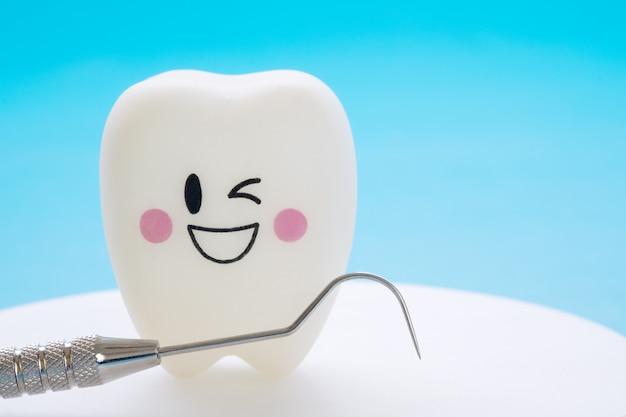 Chiuda sugli strumenti di dental e sui denti di sorriso modellano su fondo blu.