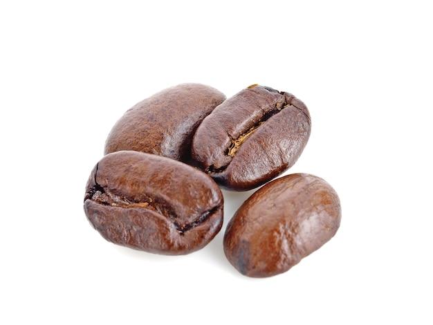 Chiuda sui chicchi di caffè arrostiti isolati su bianco