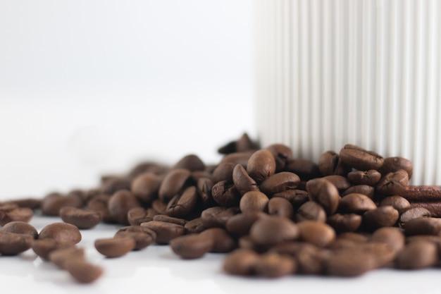 Chiuda sui chicchi di caffè e sulla tazza bianca isolati su fondo bianco.