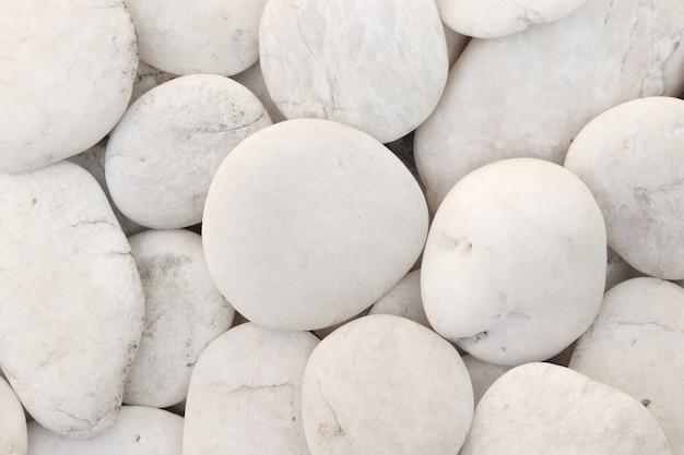 Chiuda sui ciottoli bianchi naturali, struttura della ghiaia di pietra decorativa per fondo.