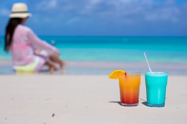 Chiuda sui cocktail saporiti sulla giovane donna del fondo della spiaggia