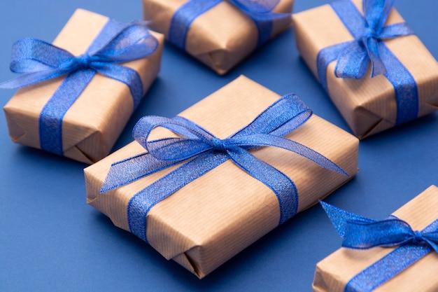 Chiuda sui contenitori di regalo, sui regali, sui contenitori di regalo avvolti carta del mestiere sul blu.