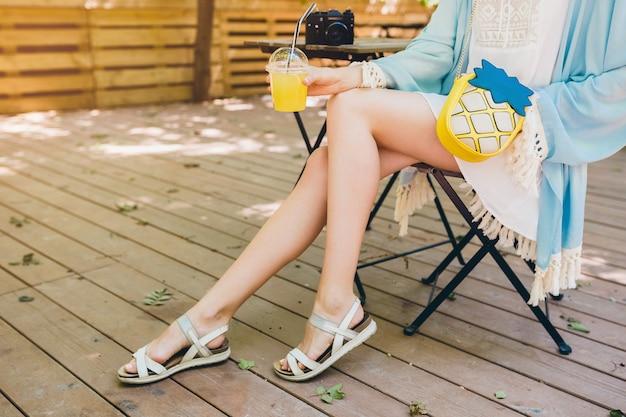 Chiuda sui dettagli della giovane donna che si siede nello sdraio in attrezzatura di modo dell'estate