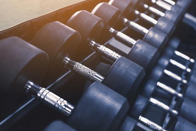 Chiuda sui dumbbells neri nella fila al centro di forma fisica di sport, attrezzatura di allenamento con i pesi nel concetto di forma fisica di sport.