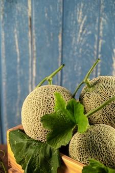 Chiuda sui meloni del cantalupo in scatola di legno sulla tavola di legno