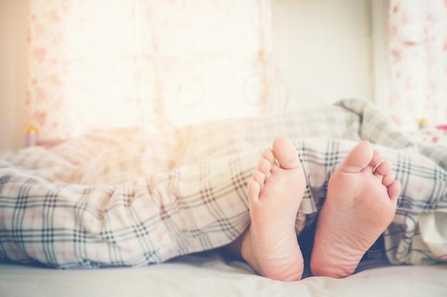 Chiuda sui piedi delle donne che dormono sul letto nella mattina