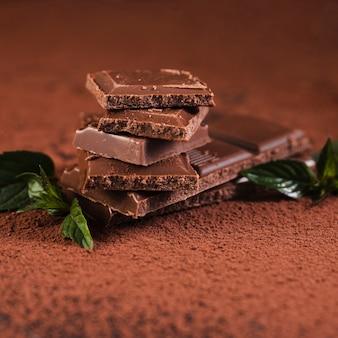Chiuda sui quadrati della barra di cioccolato su cacao in polvere