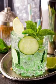 Chiuda sui retro barattoli di vetro di limonata con il cetriolo e la menta sulla tavola di legno