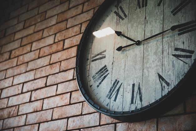 Chiuda sui retro stili d'annata dell'orologio di parete che appendono sul muro di mattoni